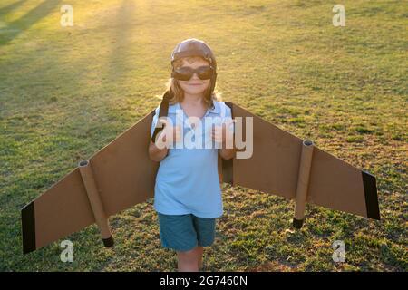 Enfant garçon jouant avec des ailes d'avion jouet. Rêve de devenir pilote. Vol super-héros. Garçon rêve de voler. Enfant insouciant jouant à l'extérieur.
