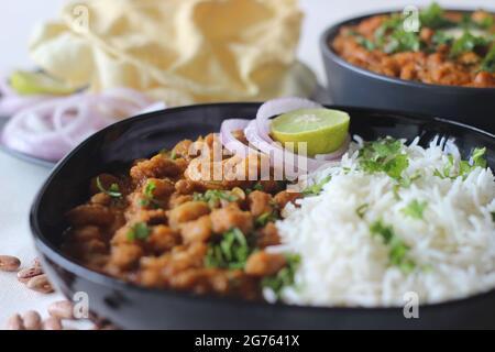 Haricots rouges dans une épaisse sauce épicée d'oignons et de tomates servis avec du riz basmati et du papad cuits à la vapeur. Communément appelé rajma masala an