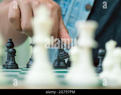Jeu d'échecs sur un plateau vert, une main tient un pion noir