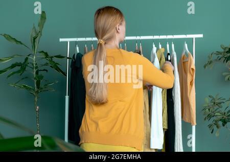 Femme blonde d'âge moyen fait du shopping et regarde la nouvelle robe jaune près de l'étagère avec des vêtements