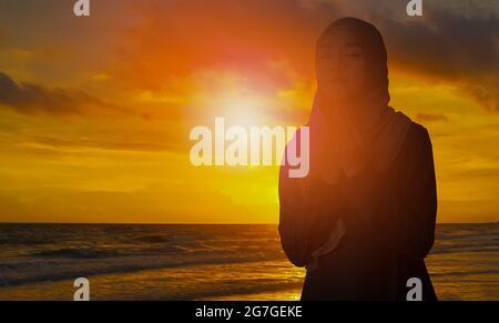 Silhouette de jeune femme musulmane dans un hijab noir, debout avec elle dos au coucher du soleil, concept rituel religieux pour la paix et la tranquillité.