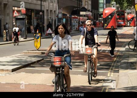 Les gens de Santander louent des vélos à vélo le long d'Oxford Street le 2 juillet 2021 à Londres, Royaume-Uni. Le programme, parrainé par Santander, est destiné à faire du vélo aux Londoniens. Dans le cadre d'une initiative majeure. Ces vélos sont chargés pour la durée de leur utilisation. Faites un cycle, montez-le là où vous le souhaitez, puis retournez-le, prêt pour la personne suivante. Disponible 24 heures sur 24, toute l'année. Il est en libre-service et il n'y a pas de réservation.