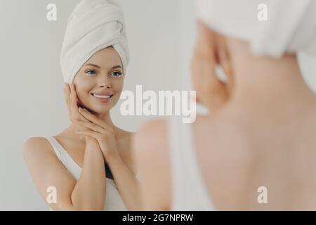 Belle femme heureuse après avoir appliqué maquillage regarder dans le miroir et sourire en se tenant dans la salle de bains