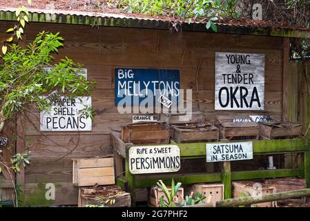 Marché agricole en bord de route avec des panneaux rustiques et pittoresques.