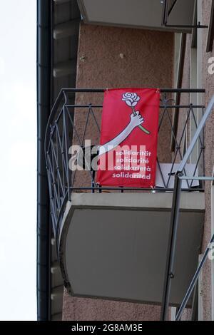 Bannière rouge avec mot solidarité en allemand, français, italien et espagnol. Au-dessus des mots, il y a une main tenant une rose. La bannière est sur le balcon.