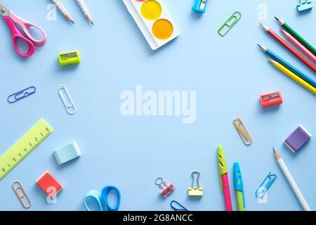 Composition de la couche plate avec fournitures scolaires sur fond bleu. Concept de retour à l'école. Vue de dessus, au-dessus de la tête.