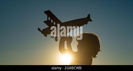 Pilote d'enfant aviateur avec l'avion rêve de voyager. Rêves d'enfant. Enfant sur fond de ciel de coucher de soleil.