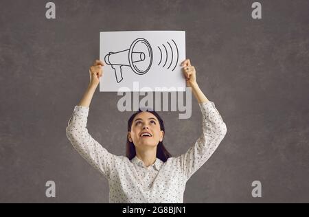 Jeune femme heureuse tenant une feuille de papier avec une photo d'un mégaphone hurant