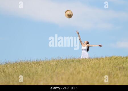 Femme excitée debout dans un champ de blé jetant le chapeau pamela à l'air