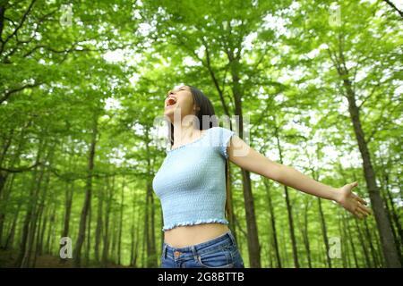 Femme asiatique excitée célébrant des vacances s'étirant les armes et hurlant dans une forêt verte