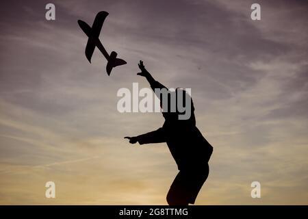 Enfant avec avion rêve de voyager en été dans la nature au coucher du soleil. Enfant actif jouant. Enfance à la campagne. Pilote aviateur enfant avec un jouet