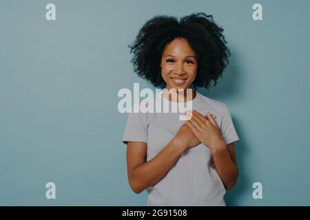 Une femme noire reconnaissante tenant les mains sur la poitrine, une femme africaine satisfaite exprimant l'amour du cœur