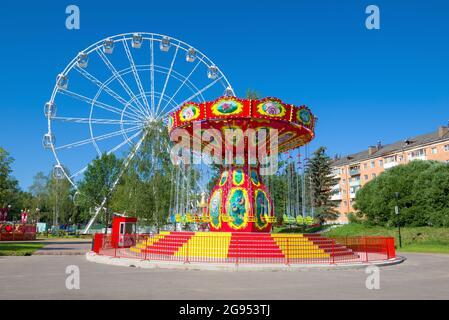 VELIKIE LUKI, RUSSIE - 04 JUILLET 2021 : carrousel coloré sur le fond de la grande roue dans le parc de la ville de la culture et des loisirs au soleil