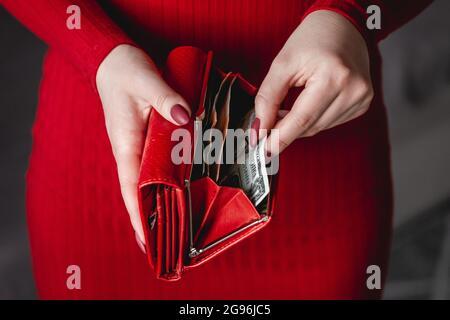 Portefeuille rouge entre les mains d'une femme dans une robe rouge avec manucure rouge