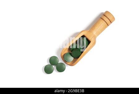 Pilules vertes de spiruline dans une cuillère en bois isolée sur un fond blanc. Comprimés de Chlorella. Vue de dessus, plan d'appartement.