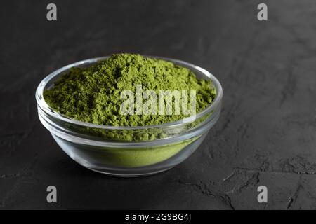 Poudre de vert de chlorelle dans un bol sur fond noir. Supplément naturel aux algues. Poudre de spiruline. Gros plan.