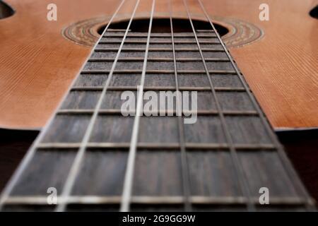 Gros plan de la vieille guitare acoustique avec focus sélectif au centre. Une perspective du cou avec un trou de son et des cordes flous. Concept de musique