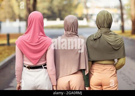 Vue arrière de trois musulmanes portant des Hijabs marchant ensemble à l'extérieur