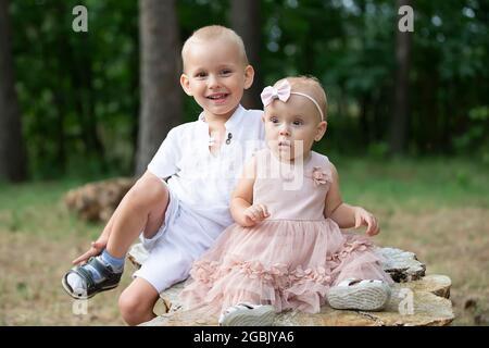 Portrait d'un frère aîné et d'une petite sœur pour une promenade dans le parc.