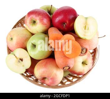 Pommes et carottes sucrées dans un panier isolé sur blanc