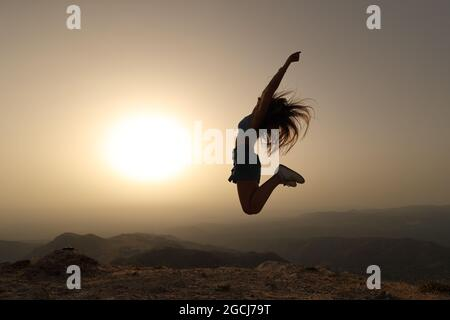 Vue latérale d'une silhouette de femme sautant au coucher du soleil dans la montagne