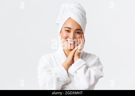 Soins personnels, beauté des femmes, concept de bain et douche. Gros plan de la belle femme asiatique heureuse dans une serviette et un peignoir touchant le visage doucement, souriant