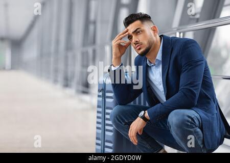Retard de vol. Un homme arabe pensif attend avec ses bagages dans le terminal de l'aéroport