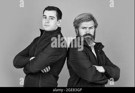 couple d'hommes posant. deux hommes ont un look sérieux. confiance et charisme. couleurs automnales grises. style automnal et printanier. look tendance pour tous