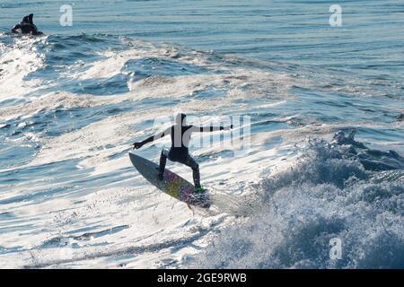Un surfeur effectuant un tour d'avion à cheval sur une vague dans la baie de Fistral à Newquay, en Cornouailles.