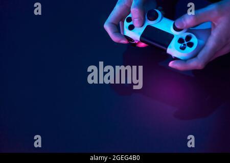 Vue en grand angle des mains mâles tenant la manette de jeu. Jeux informatiques professionnels, esport business et concept du monde en ligne.