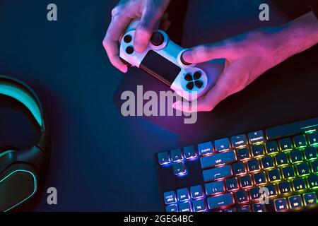 Jouer à un jeu sur ordinateur. Vue de dessus en bas des accessoires de jeu rétroéclairés. Jeux informatiques professionnels, esport business et concept du monde en ligne.