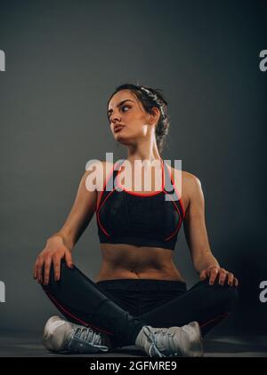 Grands progrès. Jeune belle femme en vêtements de sport qui s'étire tout en étant assise sur le sol
