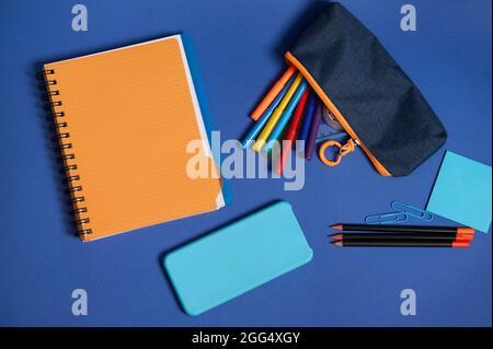 Vue du dessus des fournitures de bureau de l'école et d'un smartphone couché sur un fond bleu . Composition de la papeterie Flat lay en deux colonnes contrastées