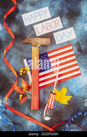 Création d'une bannière avec inscription Happy Labor Day, drapeau américain, marteau, tournevis et feuilles d'automne sur fond bleu. La fête du travail est l'Amérique et
