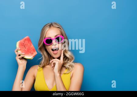 surprise jeune femme en lunettes de soleil roses tenant une tranche de pastèque isolée sur bleu
