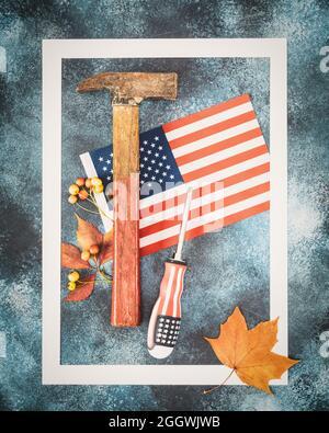 fête du travail, bannière de vacances avec drapeau américain, marteau, tournevis et feuilles d'automne dans un cadre blanc sur fond bleu. La fête du travail est l'Amérique et ca