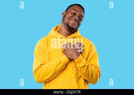 Gratitude. Heureusement, un homme afro-américain se presse les mains jusqu'à la poitrine souriant à la caméra posant debout sur fond bleu dans un studio, portant Bright Yell