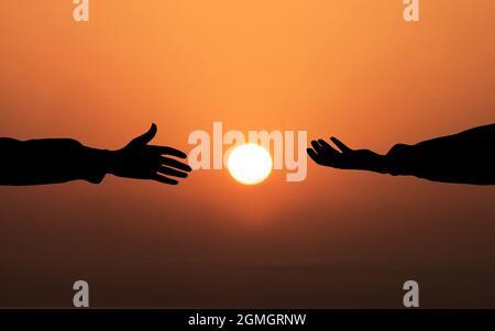 Concept d'aide à la main humaine. Mains s'aidant les unes les autres sur fond de coucher de soleil. Les gens aidant, Dieu salut et obtenir des concepts loués