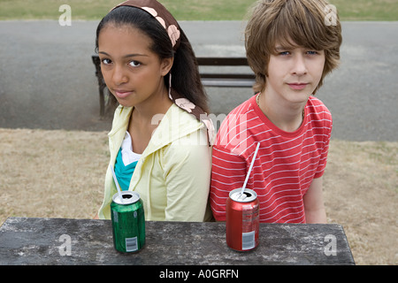Teenage boy and girl avec boissons Banque D'Images