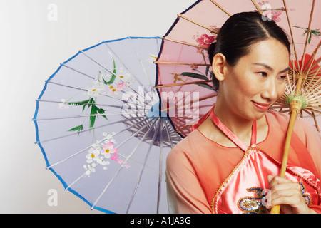 Close-up of a Mid adult woman holding des parapluies et souriant Banque D'Images