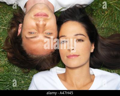 Jeune couple resting on grass Banque D'Images