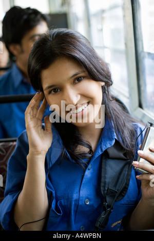 Female student listening to mp3 player sur le bus Banque D'Images