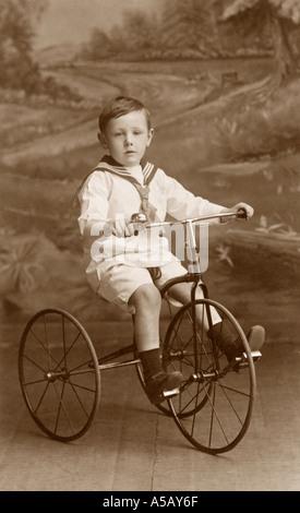 Début des années 1900, studio portrait de jeune garçon vêtu d'un costume de marin équitation son jouet tricycle, Banque D'Images