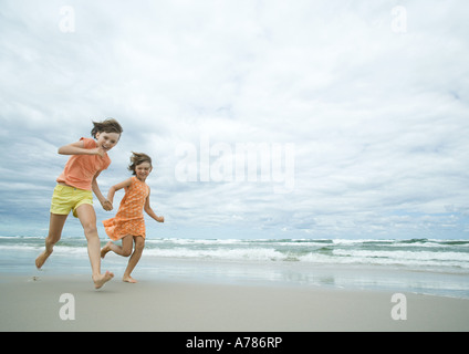 Deux filles exécutant la main dans la main sur la plage, pleine longueur Banque D'Images