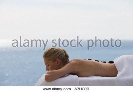 Une jeune femme recevant un traitement holistique aux pierres chaudes Banque D'Images