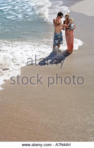 Family standing on beach in surf femme transportant fille 2 4 Augmentation de la vue Banque D'Images