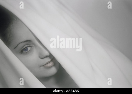 Woman peering out à travers des rideaux blancs Banque D'Images