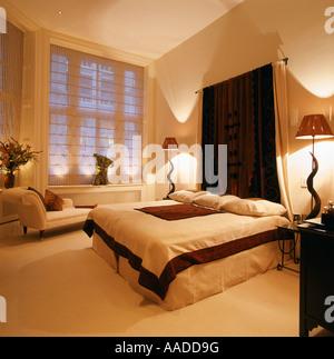 Tête de lit en tissu accroché au-dessus du divan dans la chambre avec des lampes et chaise longue fenêtre ci-dessous Banque D'Images