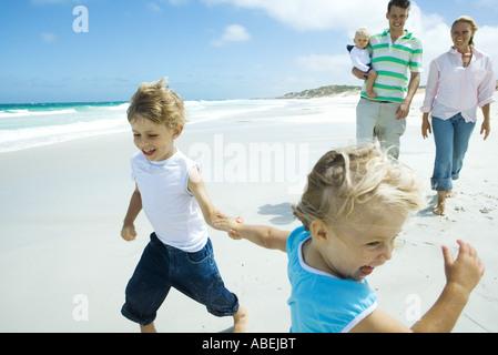 Frère et sœur d'exécution et de rire sur la plage en face des parents avec bébé Banque D'Images