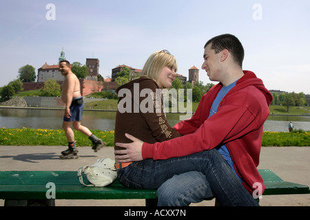 Jeune couple assis sur un banc, dans l'arrière-plan le château de Wawel, à Cracovie, Pologne Banque D'Images
